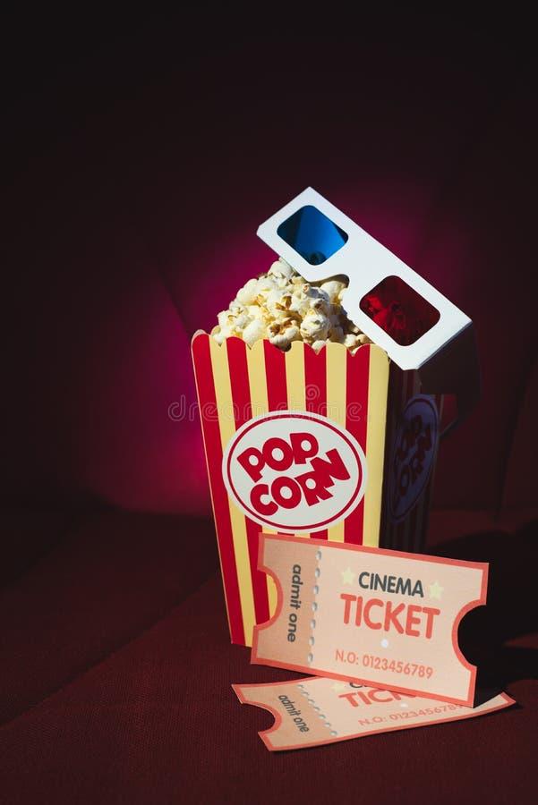 戏院的玉米花和3d玻璃在戏院的扶手椅子 免版税库存图片