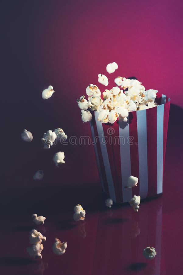 戏院跳跃在红色背景中的玉米花 免版税库存图片