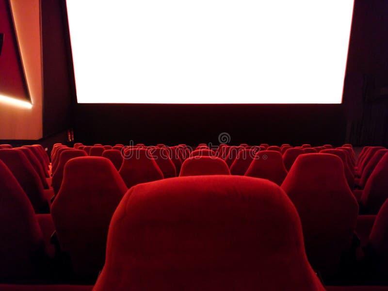 戏院-一家电影院的内部有空的红色和黑位子的与白色屏幕-大模型屏幕 免版税库存图片