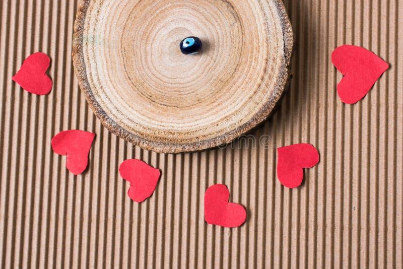 成串珠状在日志片断与红色纸心脏的 免版税库存图片