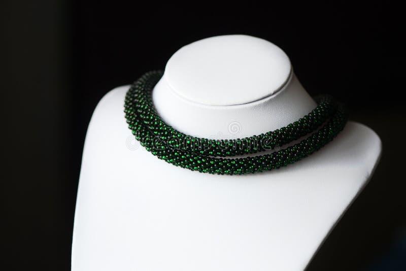 成串珠状在黑暗的背景的钩针编织项链绿色 免版税图库摄影