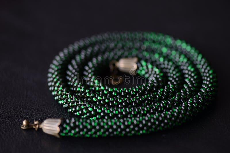 成串珠状在黑暗的背景的钩针编织项链绿色 库存照片