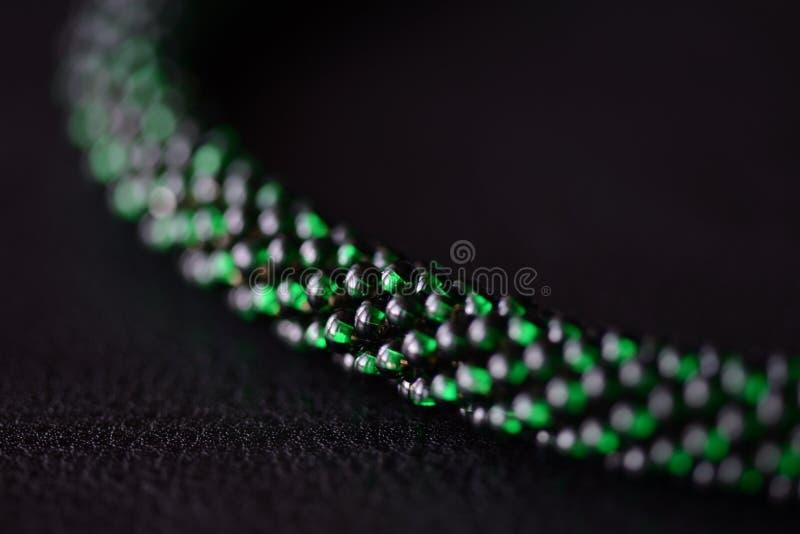 成串珠状在黑暗的背景的钩针编织项链绿色 免版税库存图片