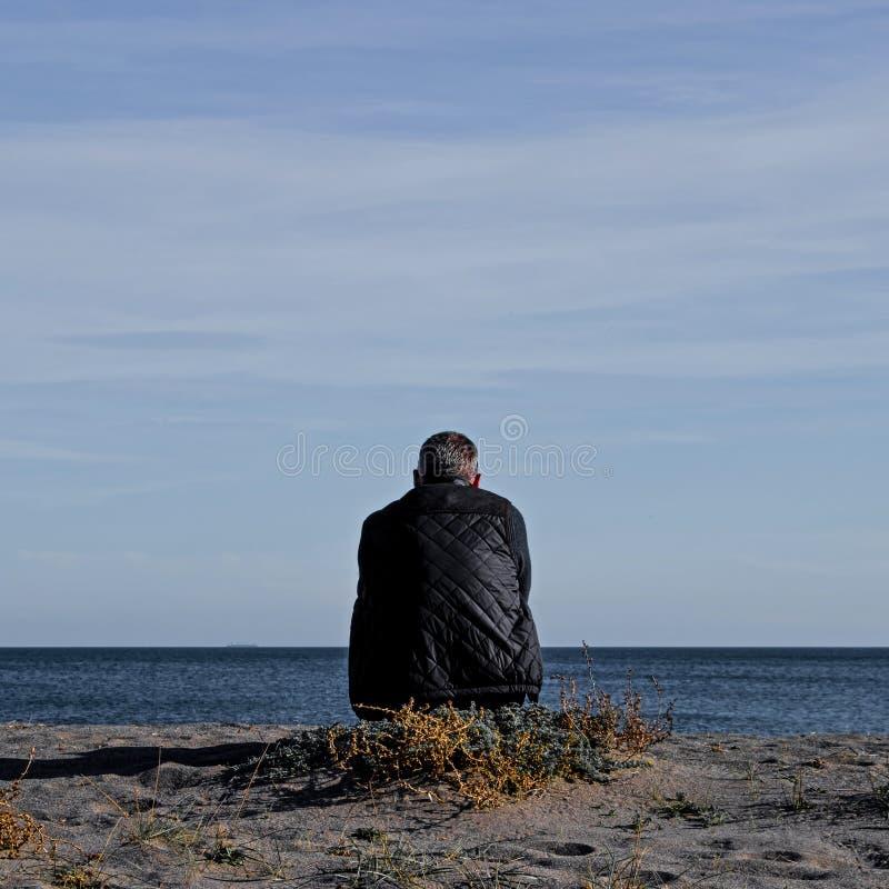 成为不饱和的观点的一个唯一人坐在一个空的海滩的象草的补丁在看对海和天空蔚蓝的安大路西亚 免版税库存照片