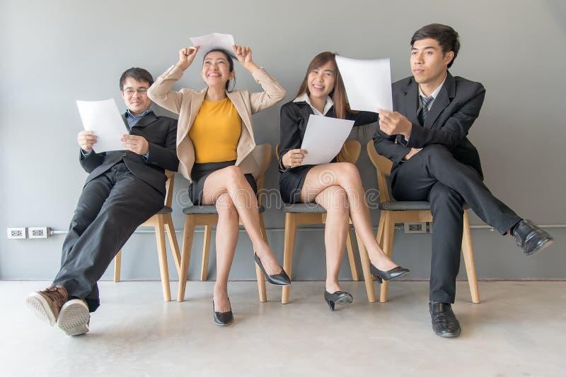成为歇斯底里的面试工作一他们 小组亚裔人民回顾文件,当等待工作面试时 库存照片