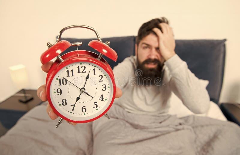 成为的技巧一个早期的造反者 人有胡子的行家困面孔在与闹钟的床上 问题的清早 免版税图库摄影