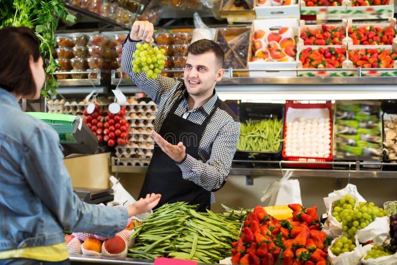 成人买果子的人卖主帮助的顾客 免版税库存照片