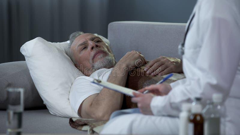 成人人说谎在长沙发和谈话与关于健康问题的疾病医生, 免版税库存图片