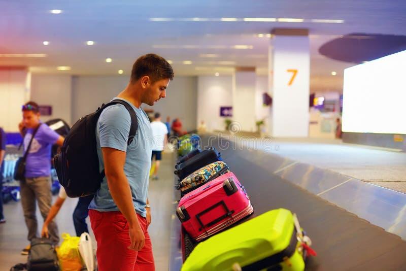 年轻成人人,乘客等待的行李在机场终端 免版税库存照片