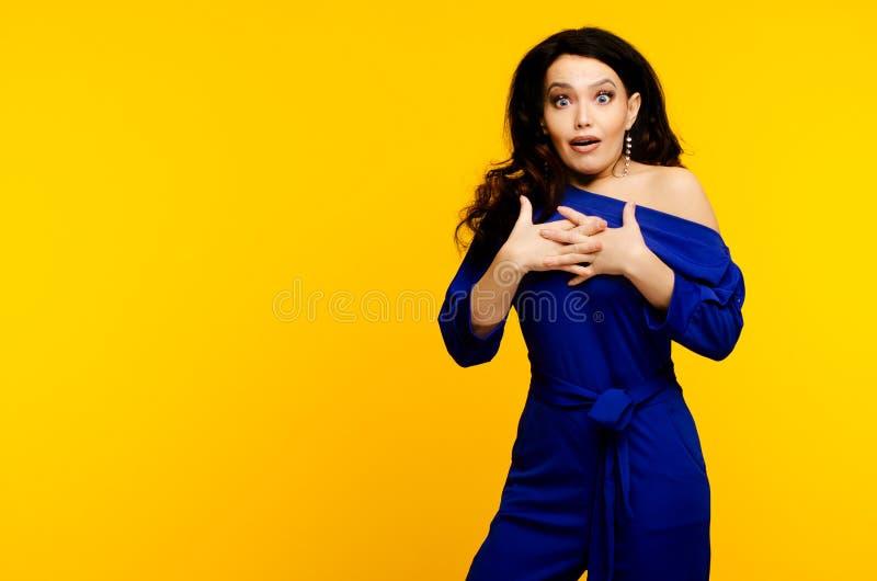 成人使蓝色衣服的妇女惊奇在黄色背景 免版税图库摄影