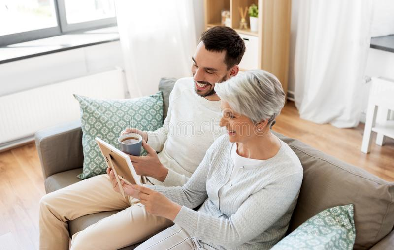 成人儿子和资深母亲有照片的在家 免版税图库摄影