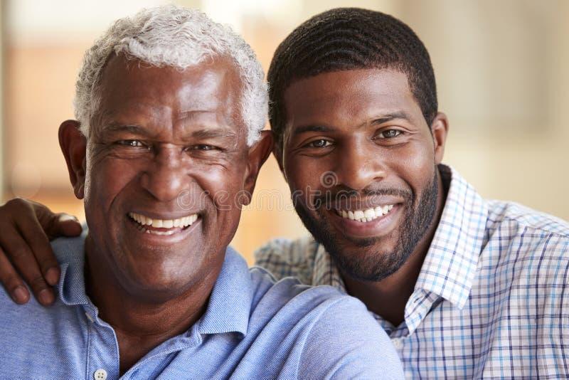 成人儿子在家拥抱的微笑的资深父亲画象  免版税库存图片