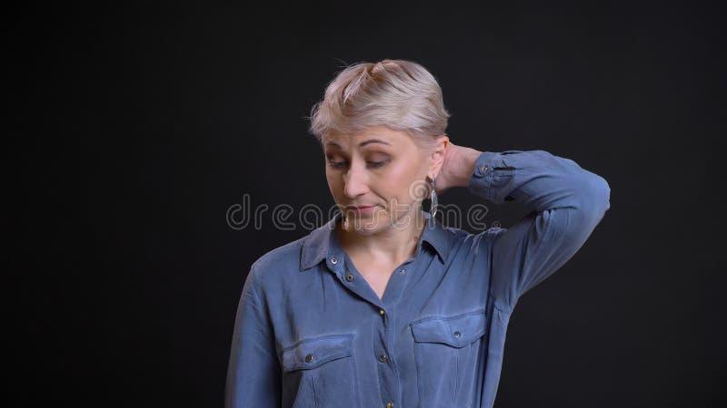 成人可爱的白种人女性特写镜头画象有短的金发的被混淆和困惑与背景 免版税库存图片