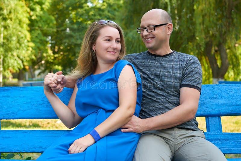 成人夫妇在城市公园,夏天,浪漫坐长凳并且爱概念、愉快的人男人和妇女 图库摄影