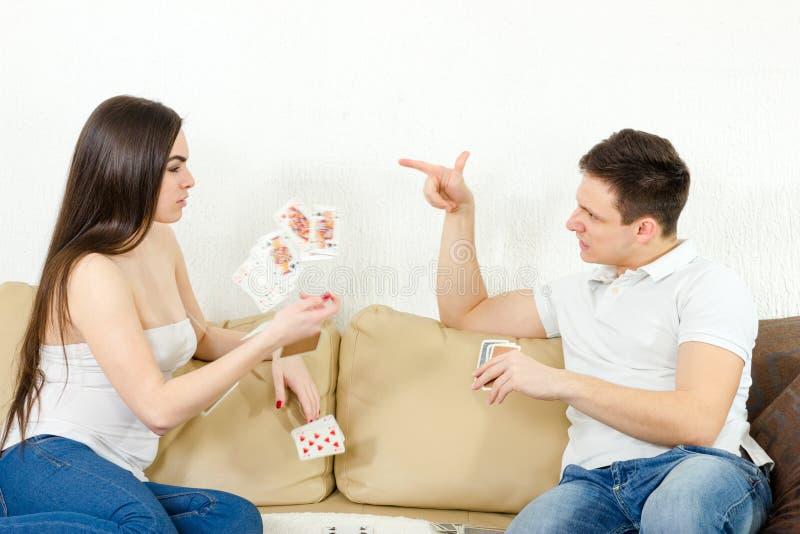 年轻成人夫妇战斗在愚笨的打牌 免版税库存图片