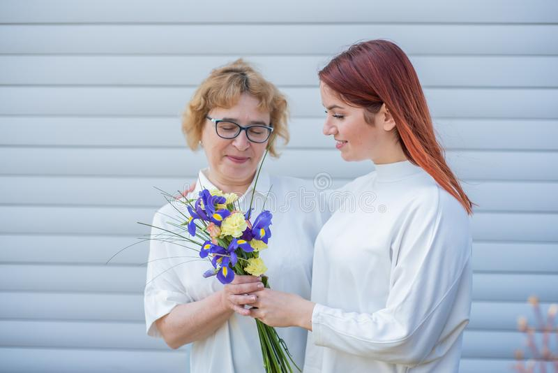成人女儿给花她的母亲外面,在房子的庭院里 r 库存照片