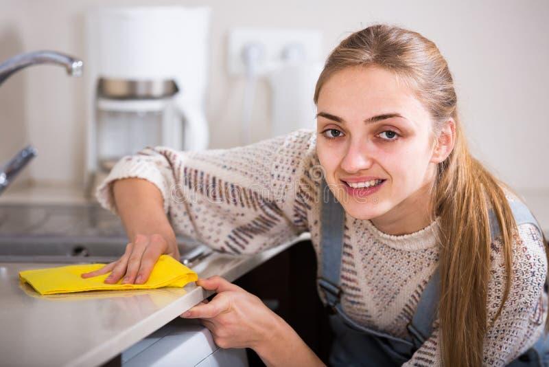 成人女孩打扫灰尘表面在住宅厨房里 免版税库存图片