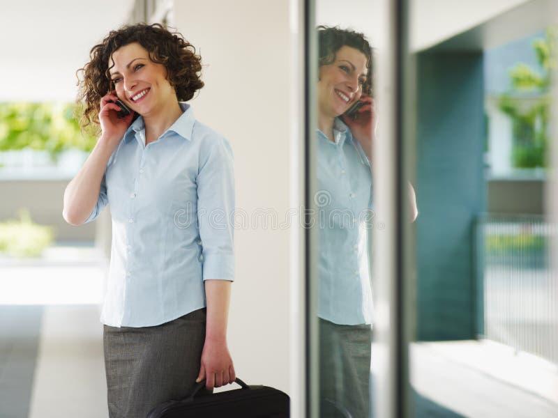 成人女实业家中间电话 免版税图库摄影