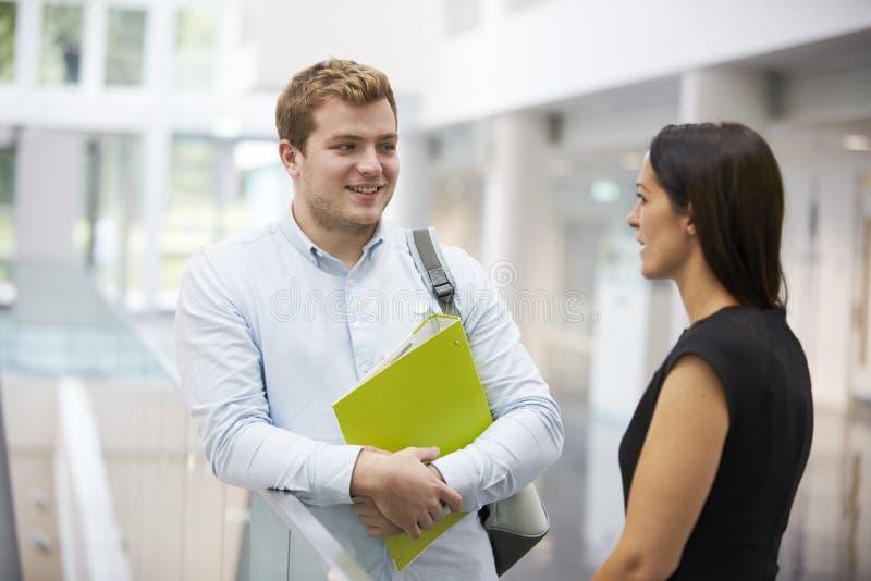 成人学生和老师谈话在大学休息室 免版税库存照片