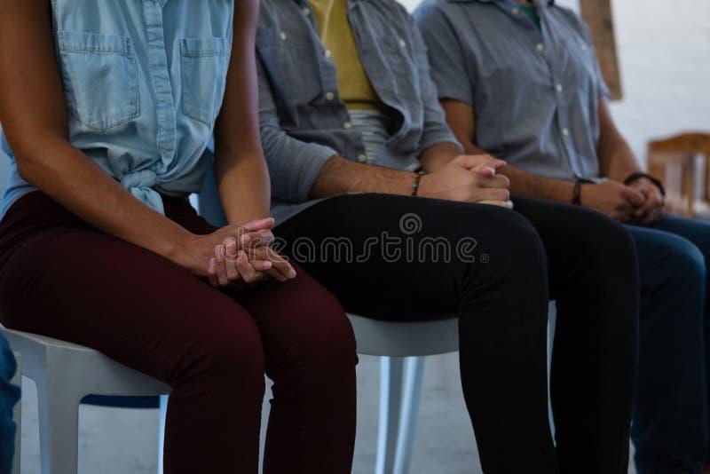 成人学生的中间部分用手扣紧了坐椅子 免版税库存照片