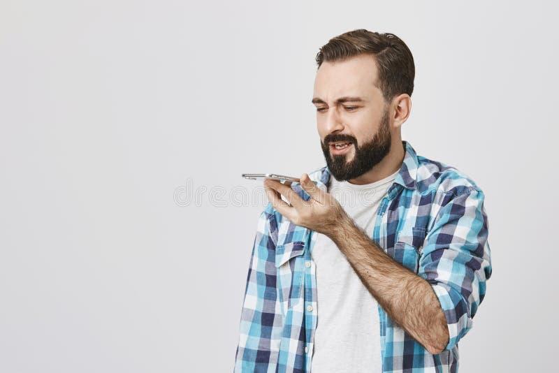 成人有胡子的男性式样举行的智能手机演播室画象在嘴附近的,当讲话在它与困惑的表示时 免版税库存照片