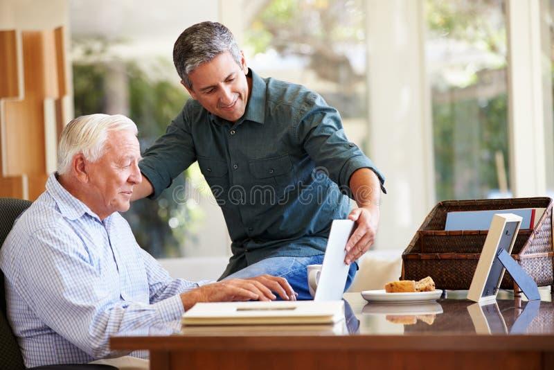 成人有膝上型计算机的儿子帮助的父亲 库存图片