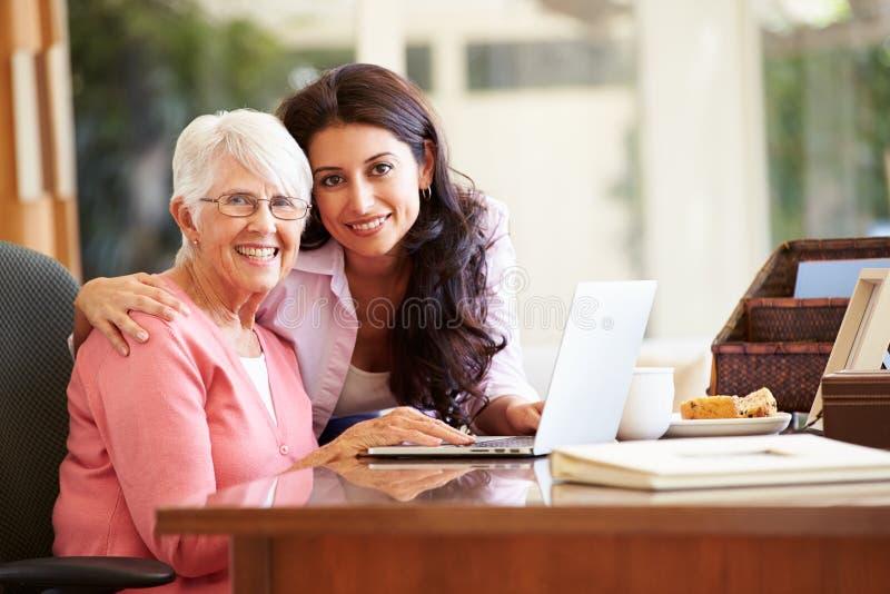 成人有膝上型计算机的女儿帮助的母亲 库存照片