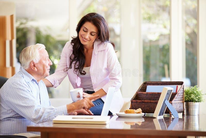成人有膝上型计算机的女儿帮助的父亲 免版税库存图片