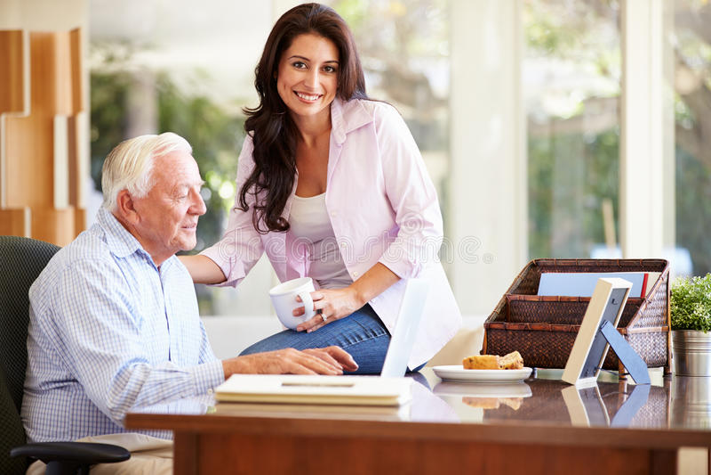 成人有膝上型计算机的女儿帮助的父亲 库存照片