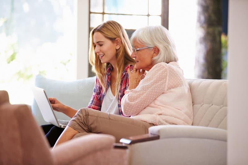 成人有计算机的孙女帮助的祖母 库存照片