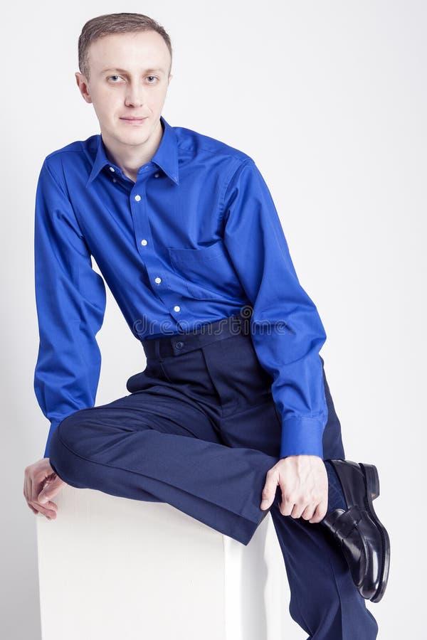 年轻成人概念 摆在蓝色衬衣和深蓝丝光斜纹棉布的英俊的白种人人画象  库存图片