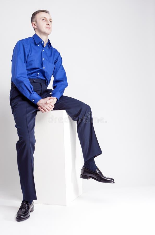 年轻成人概念 英俊的白种人人全长画象用摆在蓝色衬衣的被折叠的手 库存图片