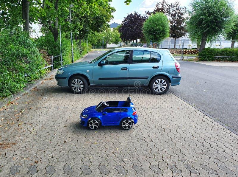 成人汽车和汽车孩子的在停车场停留近 免版税图库摄影