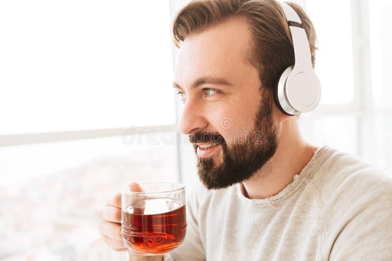 成人满意的人30s用短的棕色头发饮用的茶和l 免版税图库摄影