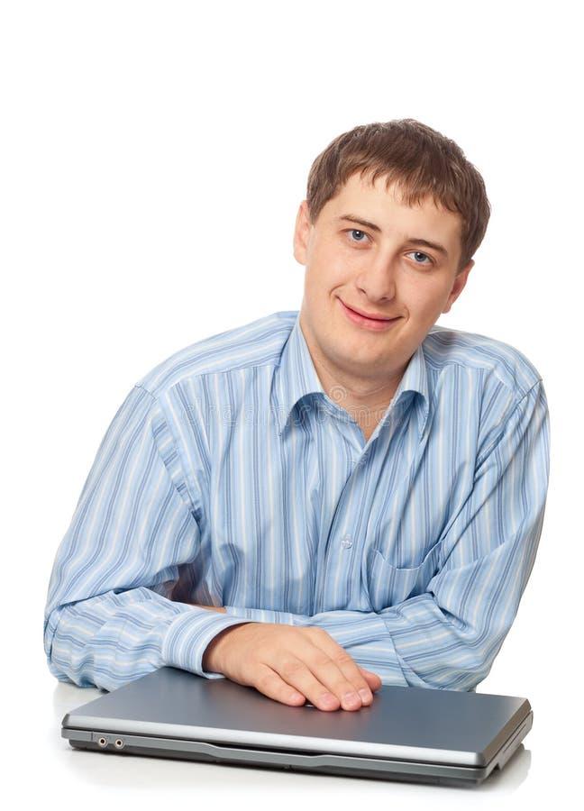 成人生意人闭合的膝上型计算机坐的年轻人 库存图片