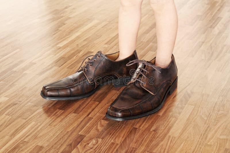 成人穿上鞋子小孩佩带 免版税库存照片
