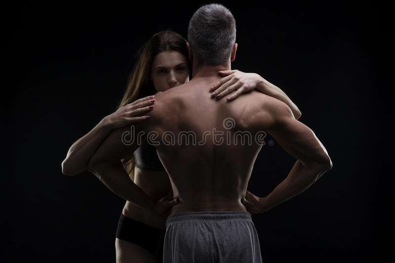 年轻成人肌肉男人和妇女 在黑背景的性感的夫妇 免版税库存图片