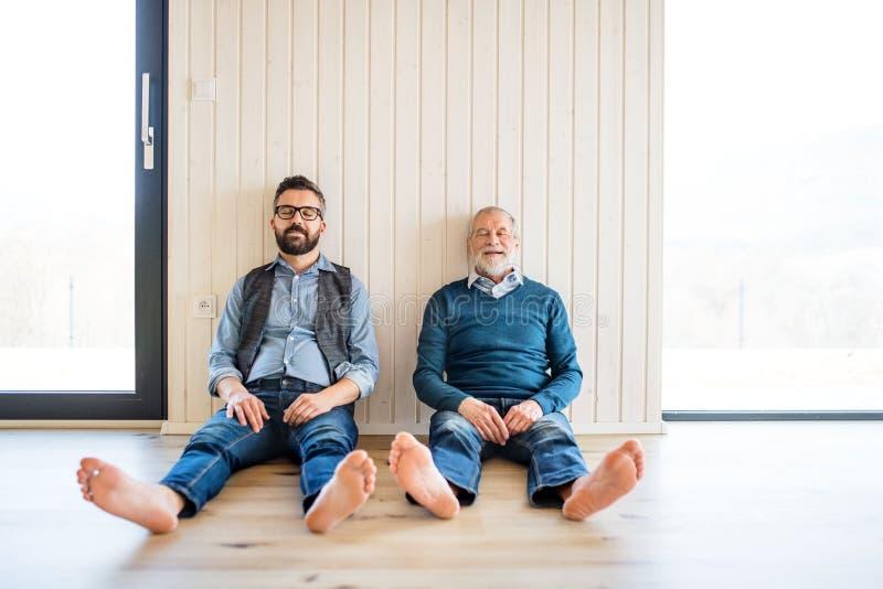 成人行家儿子和资深父亲画象坐地板户内在家 库存照片