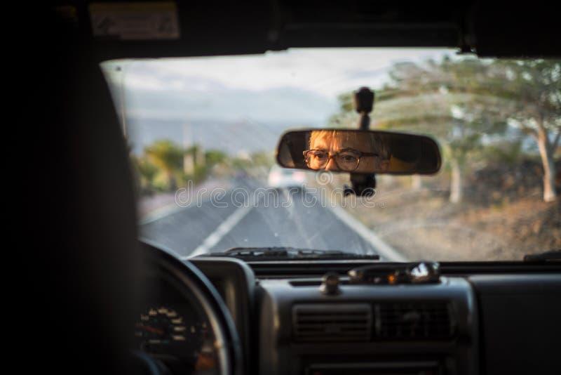 成人资深妇女驾驶汽车 在与焦点的观点里面在看她的被集中的面孔和表示一会儿的镜子 免版税库存图片