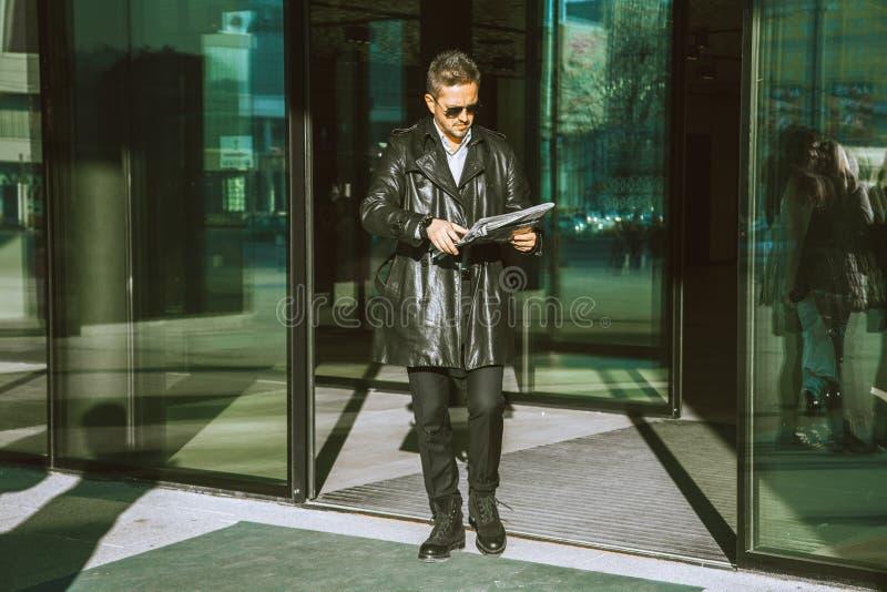 成人魅力人从与报纸的门走出去在手上 免版税库存图片