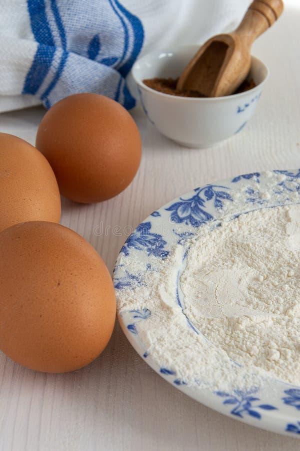 成份垂直的顶视图酥皮点心、红糖、鸡蛋和面粉的在蓝色盘 图库摄影