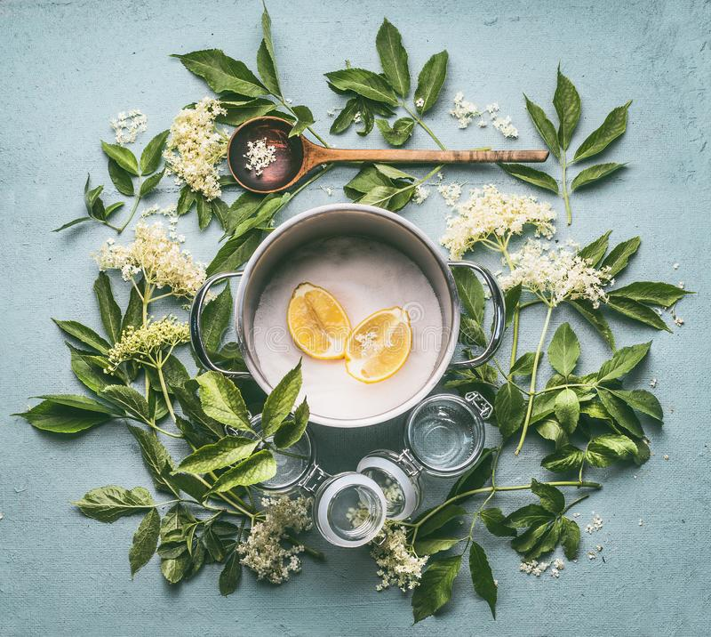 成份平的位置季节性传统做的糖浆和接骨木浆果花:烹调罐,木匙子,糖,柠檬 免版税库存图片
