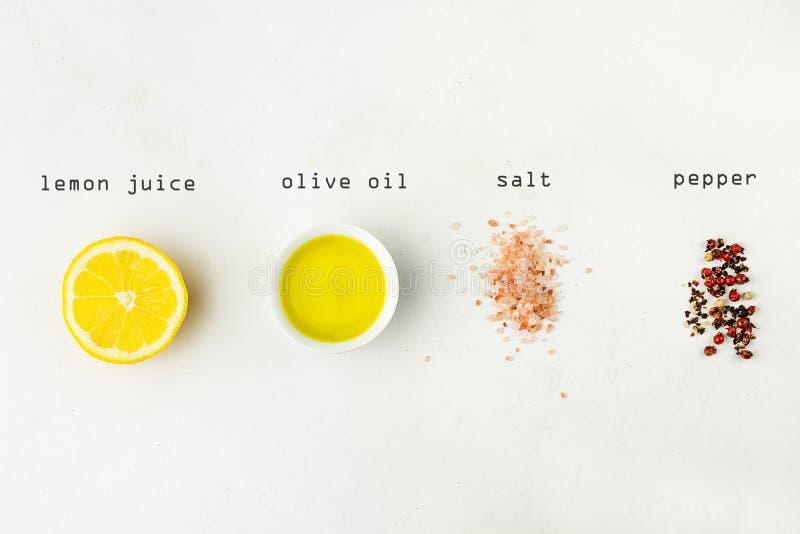 成份平的位置香醋调味汁的 柠檬,橄榄油,喜马拉雅在白色石背景的盐红色黑白胡椒 免版税库存照片
