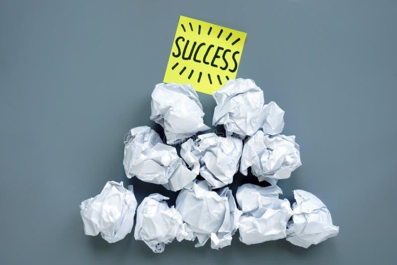 成功和失败在事务 从纸球的金字塔和在上面的备忘录棍子 免版税库存照片
