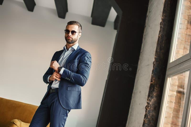 成功和金钱 年轻和可爱的商人在时髦的衣服的办公室站立并且通过看照相机 库存照片