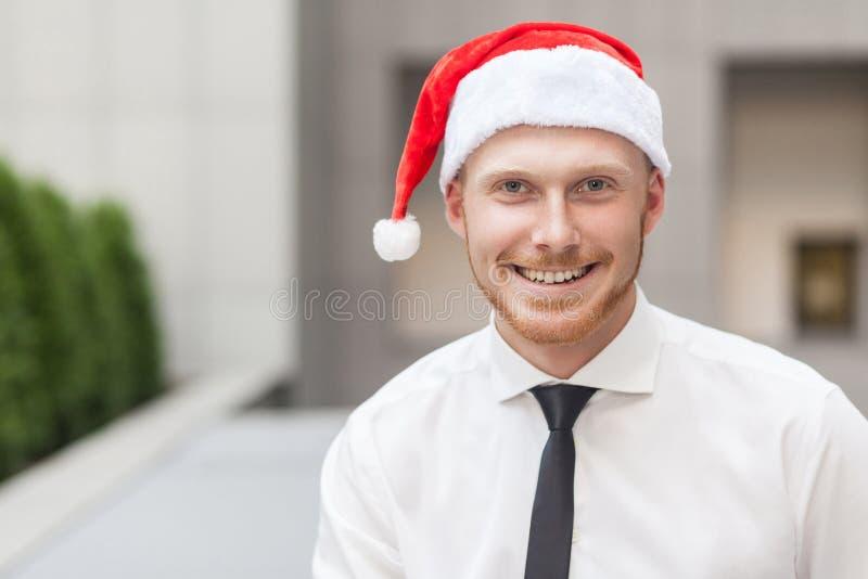 成功在圣诞老人帽子的姜商人画象  看照相机和暴牙的微笑 图库摄影
