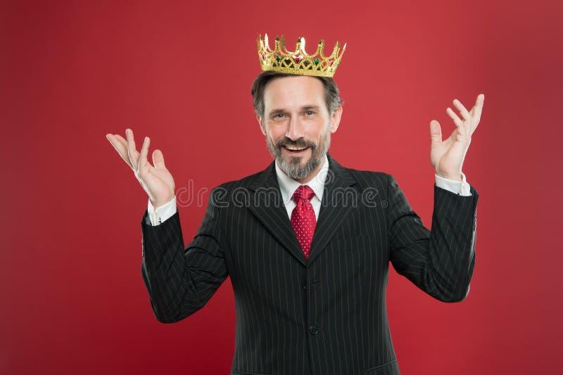 成功奖励了他的努力 成熟在红色背景的人佩带的皇冠上的宝石 享受成功的成功的商人 免版税库存图片
