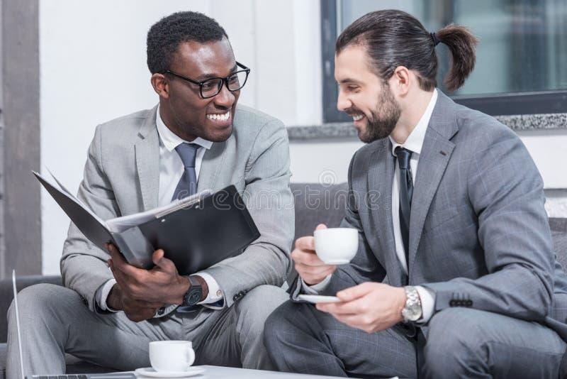 成功的不同种族的商人坐长沙发,微笑的和饮用的咖啡 库存图片