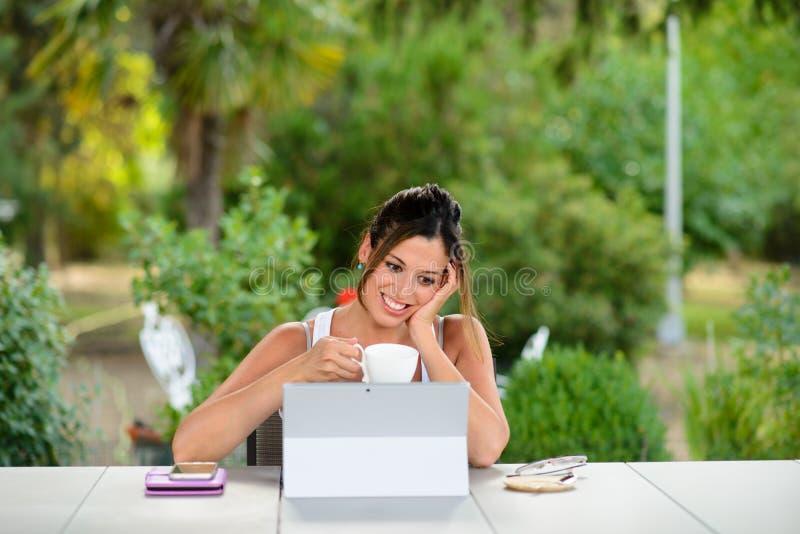 成功的专业偶然妇女在网上与膝上型计算机一起使用 免版税库存照片