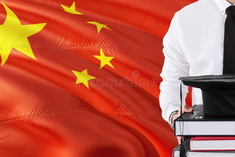 成功的中国学生教育概念 拿着书和毕业盖帽在中国旗子背景 免版税库存图片